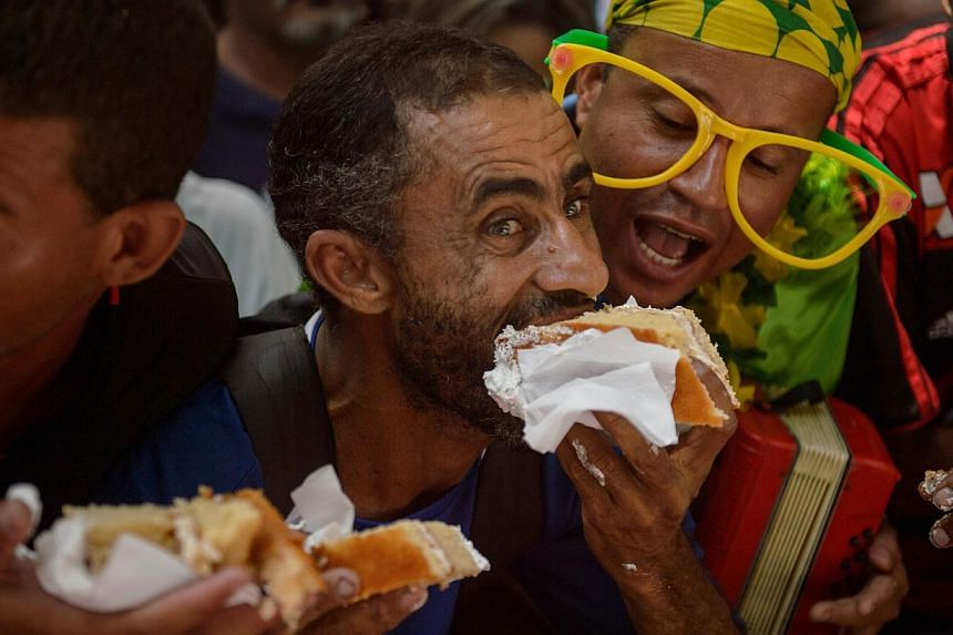 A man stuffing himself with cake at the celebrations to make the day Rio was founded, on March 1, 1565, by Portuguese explorer and city founder Estacio de Sa. -- PHOTO: AFP