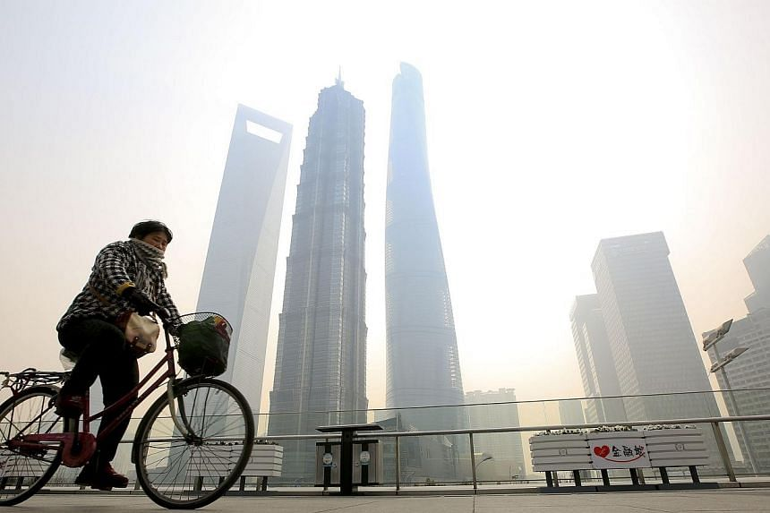 A woman covers her nose and mouth with her scarf amid heavy haze, as she rides a bicycle at the Pudong financial area in Shanghai on Feb 12, 2015. A former television presenter in China, inspired by her sick daughter, has produced a documentary video