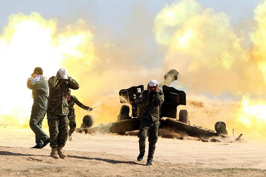 Volunteer Shiite fighters, who support the Iraqi government forces in the combat against ISIS, firing a Howitzer artillery canon in the village of Awaynat near the city of Tikrit on Feb 28, 2015.-- PHOTO: AFP