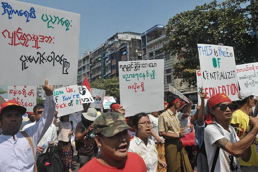 Myanmar students and nationalists hold placards as they march in protest against a national education bill in Yangon on Feb 15, 2015.Riot police sealed hundreds of Myanmar student protesters inside a monastery inLetpadan townon Mond