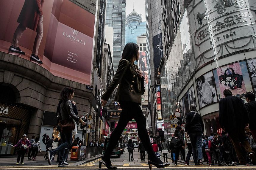 A woman crosses a street in the financial district of Central in Hong Kong on Feb 25, 2015. The Hong Kong and Singapore budgets released last week highlight some of the long-term economic challenges facing both cities - and how their respective gover