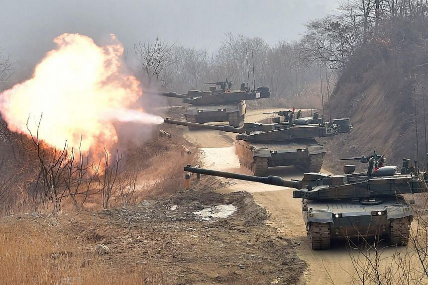 """South Korean army's K-2 tanks fire during a live-fire drill in Yangpyeong, 60 km east of Seoul, on Feb 11, 2015.North Korea on Monday fired missiles into the sea and vowed to carry out """"merciless strikes"""" against the United States and South Kor"""