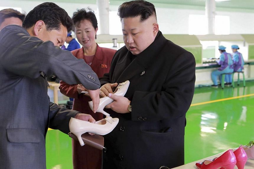 In this picture released by North Korea's Korean Central News Agency (KCNA) in Pyongyang on Jan 31, 2015, Mr Kim inspects a pair of shoes during his visit to the Wonsan Shoes Factory. -- PHOTO: REUTERS