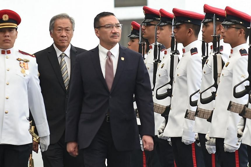 Malaysian Minister for Defence Hishammuddin Hussein (centre), accompanied by Singapore Defence Minister Ng Eng Hen (second from left), inspecting the Guard of Honour at the Ministry of Defence on March 2, 2015. -- PHOTO: MINDEF