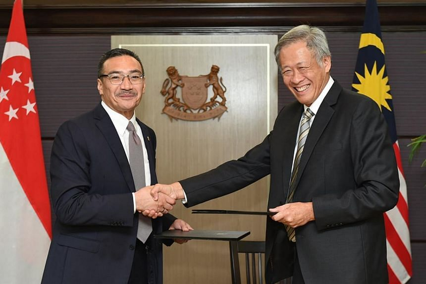 Singapore Defence Minister Ng Eng Hen (right) shaking hands with his Malaysian counterpart Hisahmmuddin Hussein after they signed a letter of intent to step up cooperation between the two countries' armed forces. -- PHOTO: MINDEF