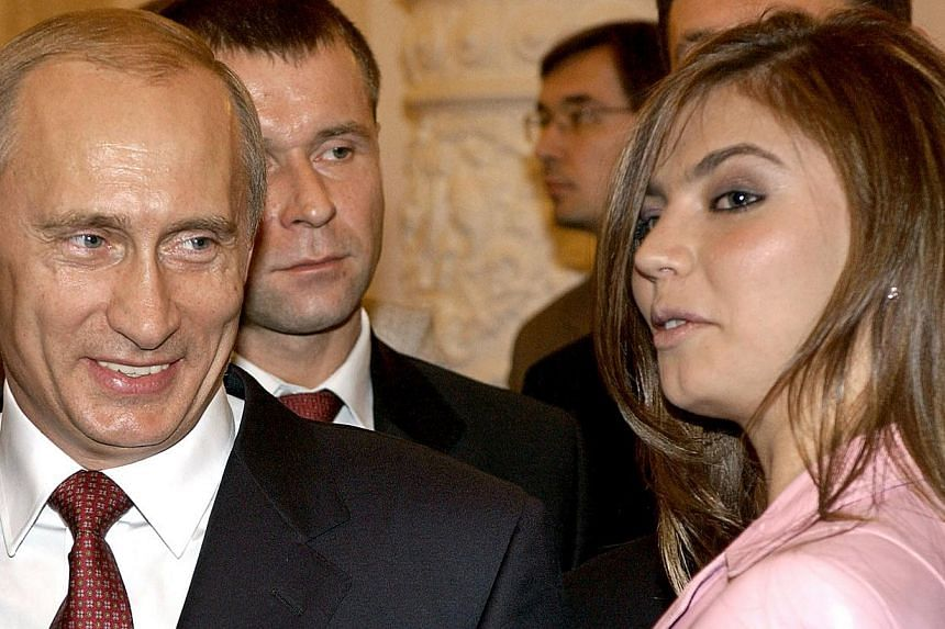 Russian President Vladimir smiles as he looks at Russian gymnast AlinaKabayeva during a meeting with the Russian Olympic team in Moscow. -- PHOTO: REUTERS