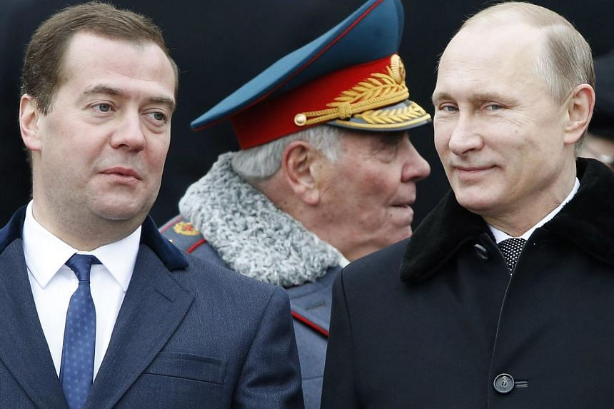 Russian President Vladimir Putin (right) and Prime Minister Dmitry Medvedev attend a wreath-laying ceremony to mark the Defender of the Fatherland Day at the Tomb of the Unknown Soldier by the Kremlin walls in central Moscow on Feb 23, 2015. -- PHOTO