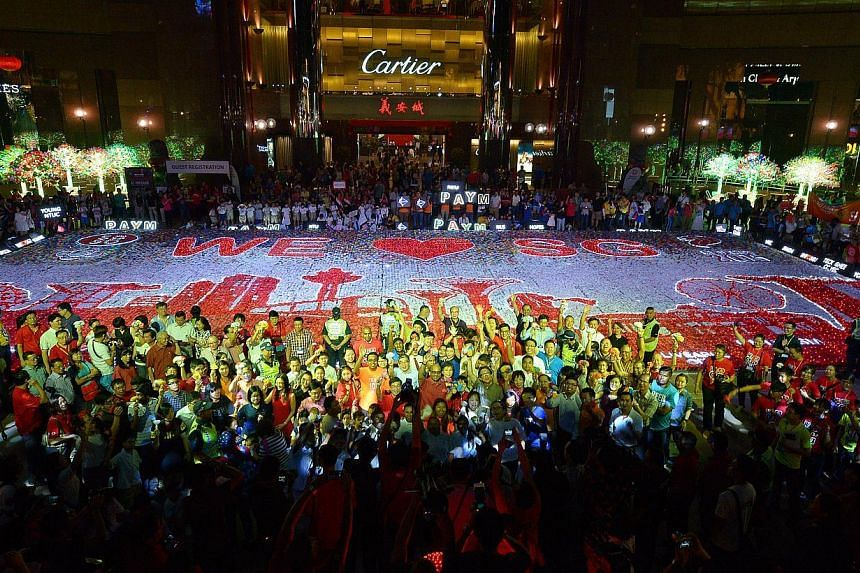 """This massive """"We Love SG"""" mural - made up of 100,000 flowers crafted from recyled plastic bags - was launched at Ngee Ann Civic Plaza by DPM Tharman Shanmugaratnam and his wife."""