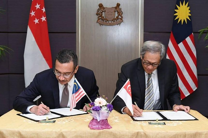 Dr Ng Eng Hen (right) and Mr Hishammuddinsigning the letter of intent to step up cooperation between Singapore's and Malaysia's armed forces.-- PHOTO:NG ENG HEN/FACEBOOK