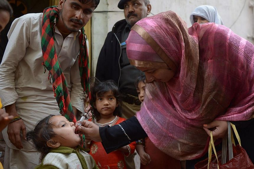 A Pakistani health worker administers polio drops to a child during a polio vaccination campaign in Karachi on Jan 20, 2015. Pakistani police arrested 471 parents who refused the vaccine, said the deputy police commissioner of Peshawar on Monday, Mar