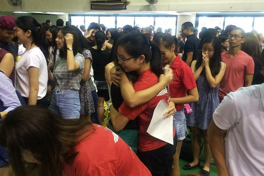 Hwa Chong institution students congratulating each other after receiving their A-level results while others wait anxiously in their school hall on Monday, March 2, 2015. -- ST PHOTO: SEAH KWANG PENG