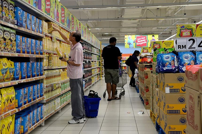 People buying groceries at Tesco in Johor Bahru's KSL City. Major supermarkets in Malaysia will be slashing prices up to 70 per cent for more than 82,000 products as part of a new national price reduction campaign. -- PHOTO: ST FILE