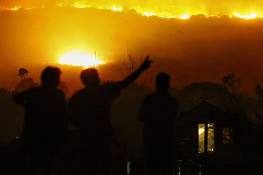 Residents stand outside their homes as a fire aproaches in Noordhoek, Cape Town, South Africa, on March 2, 2015. -- PHOTO: EPA