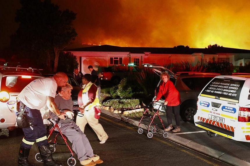 Rescue personnel evacuate old-aged pensioners from Noordhoek Manor old age home in Cape Town, South Africa, on March 2, 2015. -- PHOTO: EPA