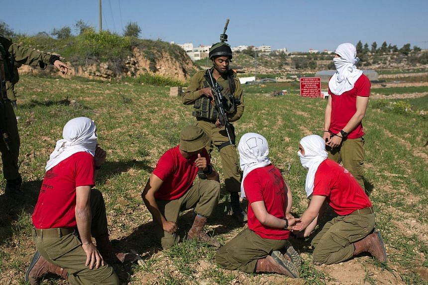 Israeli soldiers detain soldiers in red T-shirts, playing the role of Palestinian rioters, during a drill near the West Bank city of Hebron on Sunday, organised by the Israeli army to simulate dispersing of riots and crowd control. -- PHOTO: AFP