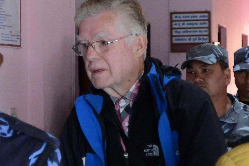 Canadian national Ernest Fenwick MacIntosh, convicted of sexually abusing a Nepalese child on Sunday is escorted by police for his appearance at the District Court in Lalitpur in a suburb of Kathmandu. -- PHOTO: AFP