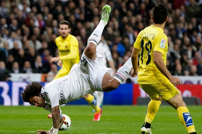 Real Madrid's Brazilian defender Marcelo (left) vies with Villarreal's defender Jaume Costa during the Spanish league football match Real Madrid CF vs Villarreal CF at the Santiago Bernabeu stadium in Madrid on Sunday. -- PHOTO: AFP