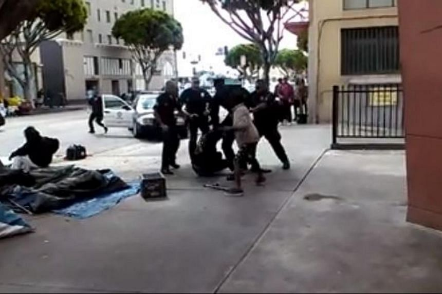 Police officers wrestling with the homeless man, whom they later fatally shot, in the background of a video posted online. -- PHOTO: SCREENGRAB FROM FACEBOOK VIDEO