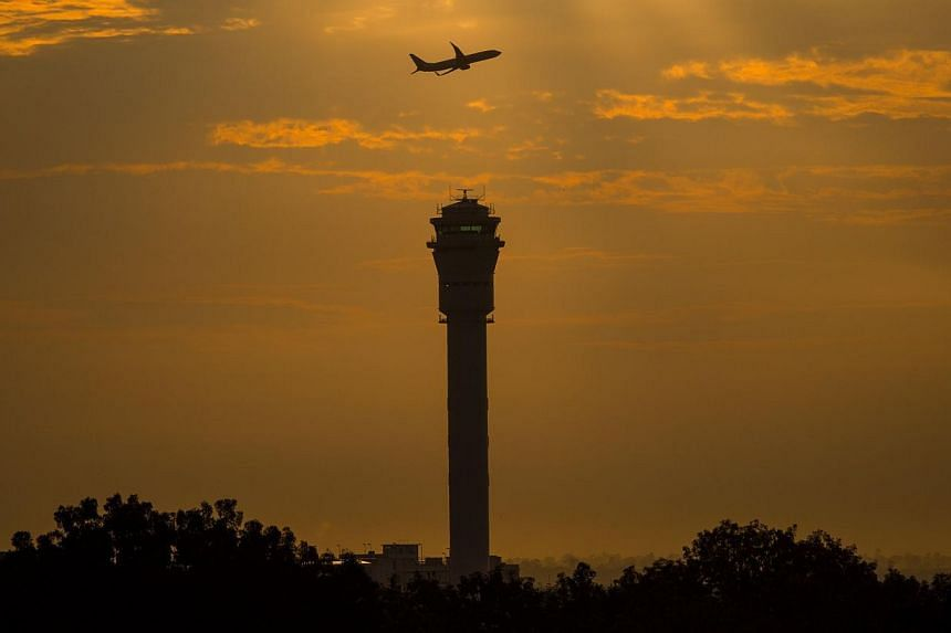 A plane flying past a control tower at Kuala Lumpur International Airport (KLIA). -- PHOTO: AFP