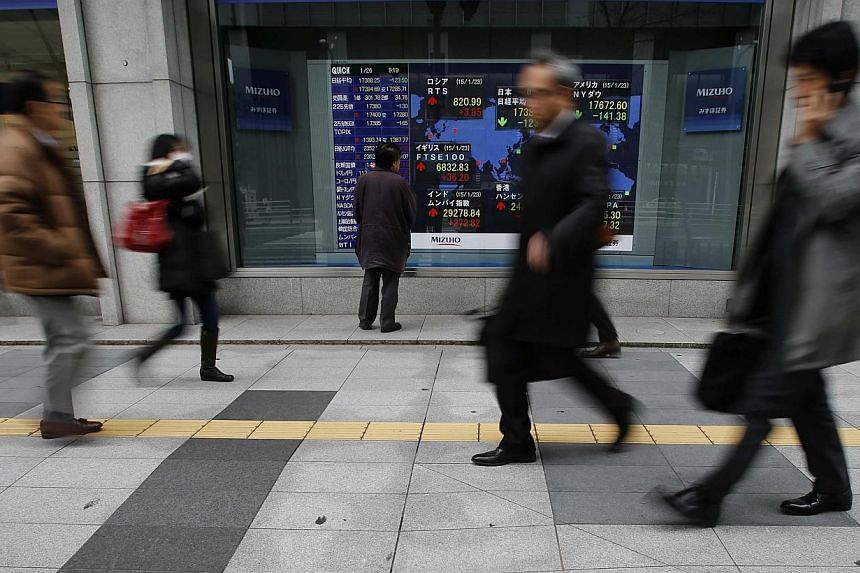 A man looking at an electronic board showing the stock market indices of various countries outside a brokerage in Tokyo on Jan 26, 2015. -- PHOTO: REUTERS