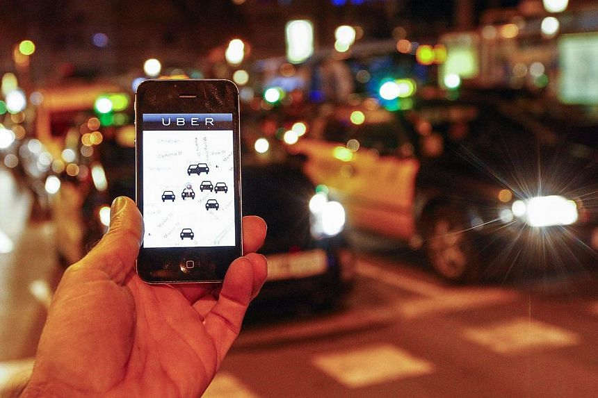 Uber helps you book a taxi or private car to take to your desired destination for a fee. -- PHOTO: AFP