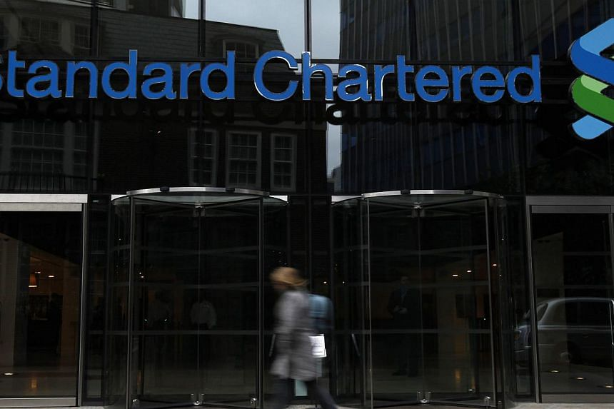 A woman walking past a Standard Chartered bank in London on Oct 13, 2010. Standard Chartered will reportedly shrink its bonus pool for 2014 by about 9 per cent to around £715 million (S$1.5 billion). -- PHOTO: REUTERS