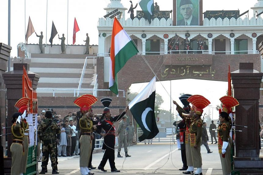 Pakistani Rangers (in black) and Indian Border Security Force personnel (in khaki) performing the flag-off ceremony during India's 66th Republic Day at the India-Pakistan Wagah Border Post on Jan 26, 2015. -- PHOTO: AFP