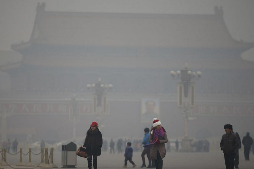 """Visitors take a walk during a polluted day at Tiananmen Square in Beijing on Jan 15, 2015. One year after """"declaring war"""" on pollution, China has appointed an inexperienced outsider - environmental scientist, Mr Chen Jining - as its new Minister of E"""