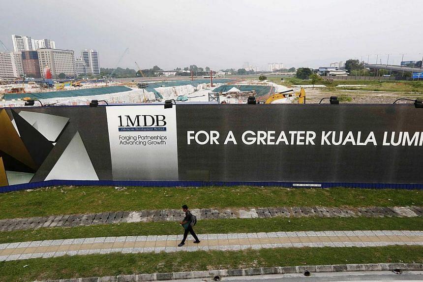A man walks past a 1 Malaysia Development Berhad (1MDB) billboard at the funds flagship Tun Razak Exchange development in Kuala Lumpur on March 1, 2015. -- PHOTO: REUTERS