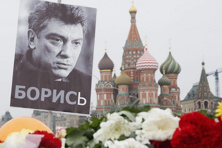 A portrait of murdered Russian opposition veteran leader Boris Nemtsov above flowers tributed in his memory at the site of his killing, with St Basil's Cathedral seen in the background, in central Moscow, Russia on March 2, 2015. -- PHOTO: EPA