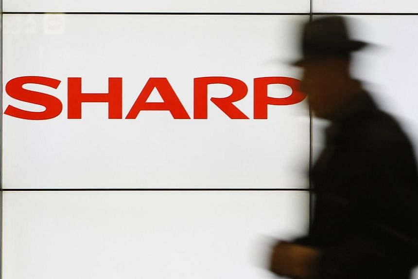 A pedestrian walks past a logo of Sharp Corp at a train station in Tokyo in this Feb 3, 2014 file photo. The company's shares tumbled nearly 10 per cent in early trade on Tuesday after the Nikkei business daily reported that the struggling electronic