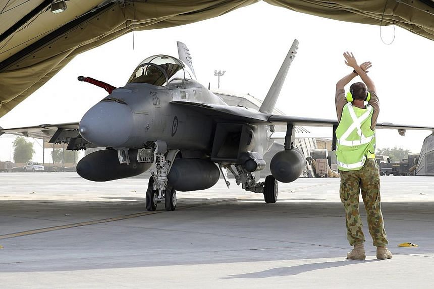 A Royal Australian Air Force (RAAF) airman marshaling a RAAF F/A-18F Super Hornet after its arrival at Al Minhad Air Base in Dubai, United Arab Emirates. -- PHOTO: EPA
