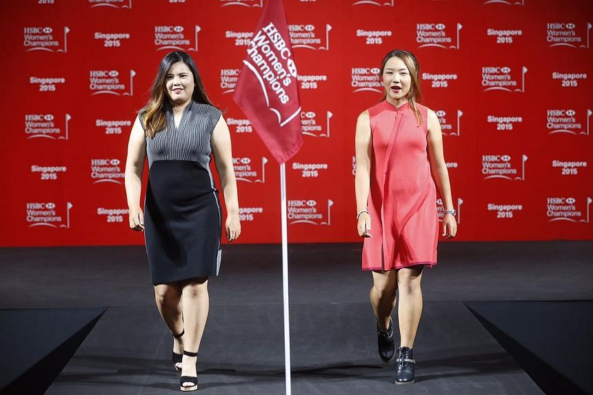 World number one Lydia Ko (right) of New Zealand and Korea's Inbee Park strut during a catwalk segment of the HSBC Women's Champions press conference at Raffles City Convention Centre on March 3, 2015. -- ST PHOTO: KEVIN LIM