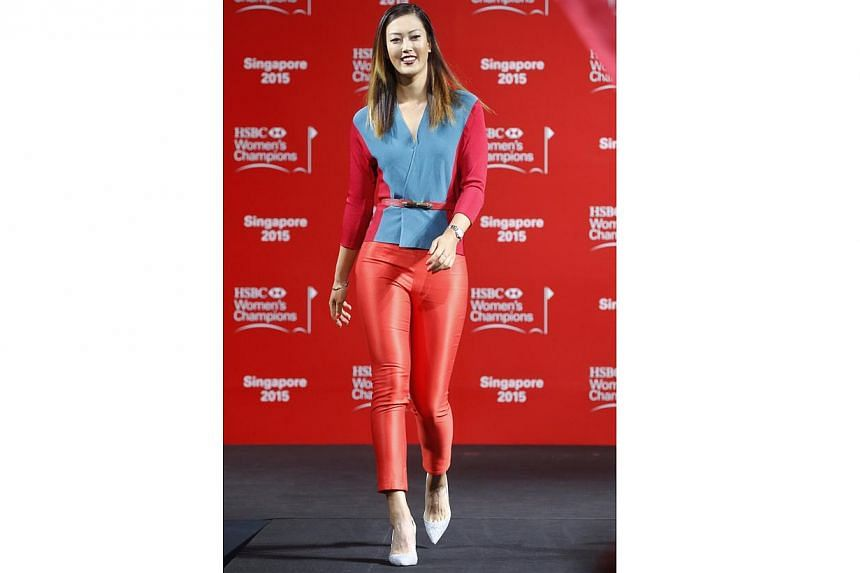 Michelle Wie struts during a catwalk segment of the HSBC Women's Champions press conference at Raffles City Convention Centre on March 3,2015. -- ST PHOTO: KEVIN LIM