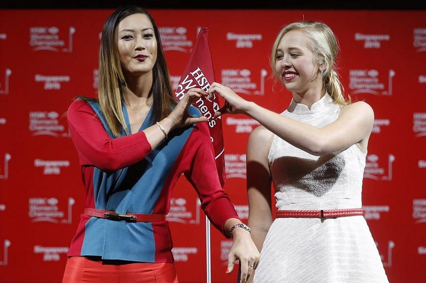 Michelle Wie (left) and Jessica Korda struck a pose during a catwalk segment of the HSBC Women's Champions press conference at Raffles City Convention Centre on March 3, 2015. -- ST PHOTO: KEVIN LIM