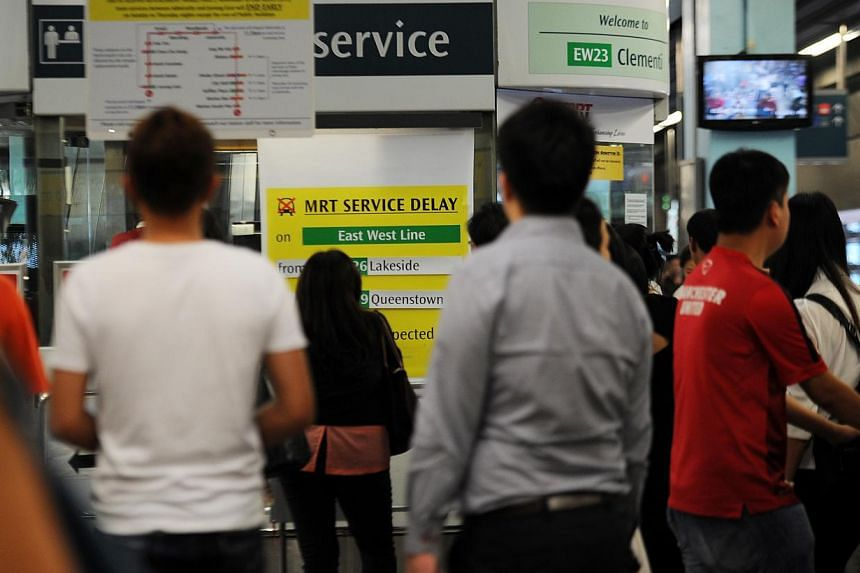 Passengers at Clementi MRT station looking at a sign indicating a train delay on the East-West line during the evening rush hour on March 3, 2015. -- ST PHOTO: TIFFANY GOH