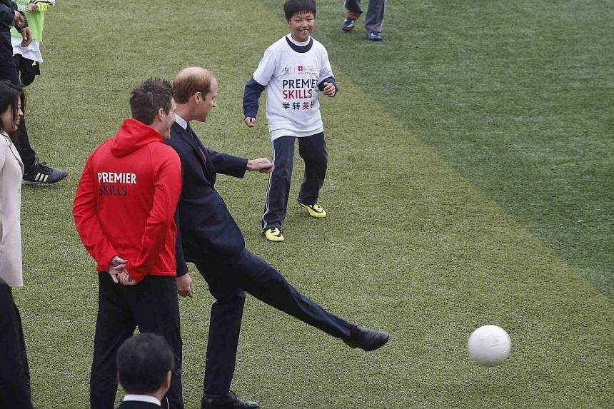 Prince William kicks a ball during a visit to a Premier League training camp at Nanyang Secondary School in Shanghai on March 3, 2015. -- PHOTO: REUTERS