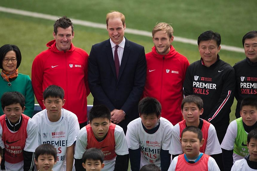 Britain's Prince William (centre, in suit with red tie) poses for a picture with students during his visit to a training session of the Premier League football camp in Shanghai on March 3, 2015. -- PHOTO: AFP
