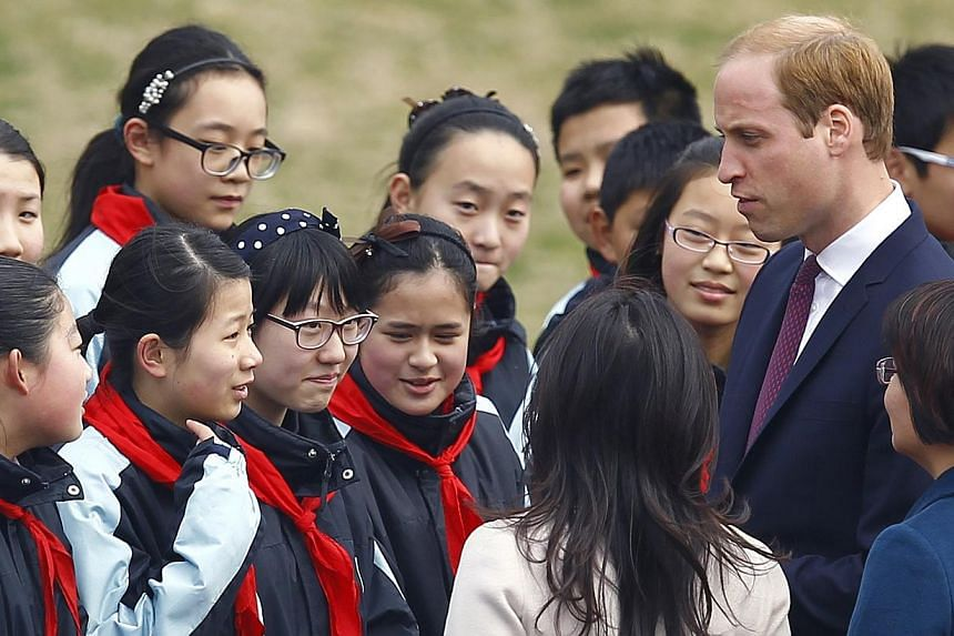 Prince William (right) chats with students during a visit to a Premier League training camp at Nanyang Secondary School in Shanghai on March 3, 2015. -- PHOTO: REUTERS