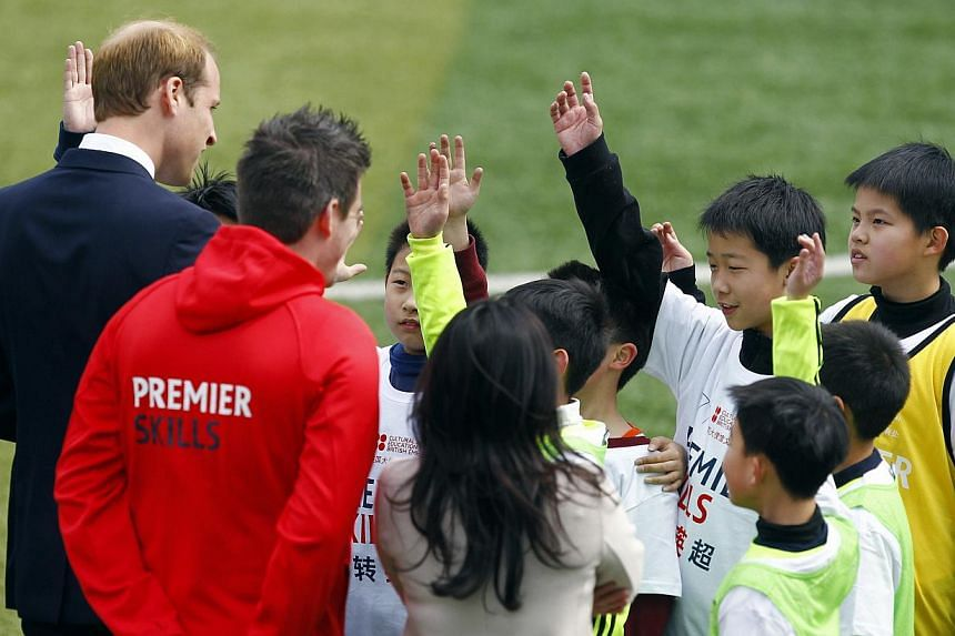 Britain's Prince William (left) chats with students during a visit to a Premier League training camp at Nanyang Secondary School in on Shanghai March 3, 2015. -- PHOTO: REUTERS
