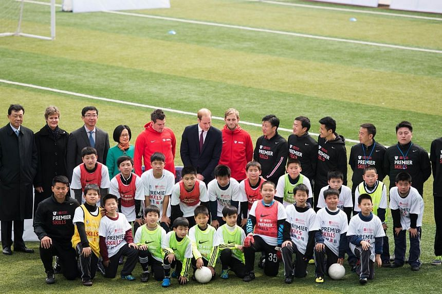 Britain's Prince William (centre, in suit with red tie) poses for a picture with students and officials during his visit to a Premier League football training camp in Shanghai on March 3, 2015. -- PHOTO: AFP
