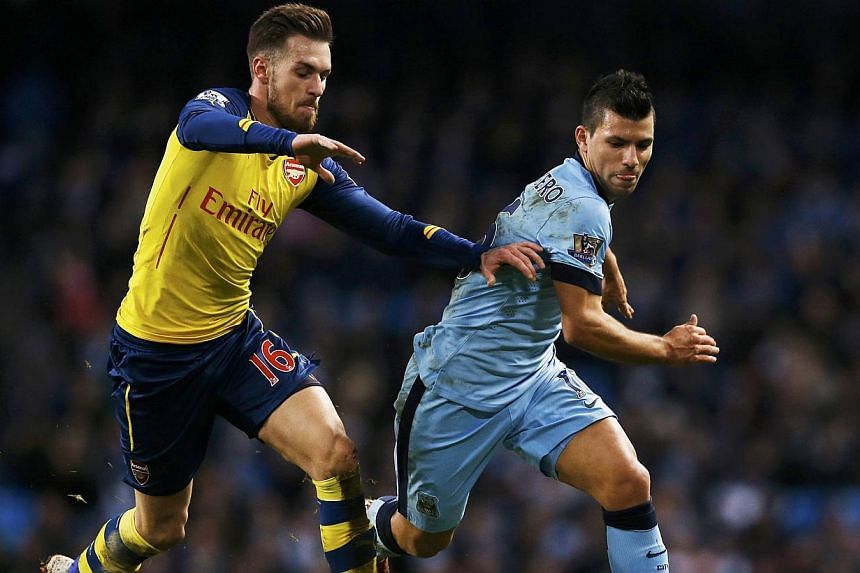 Arsenal's Aaron Ramsey (left) challenges Manchester City's Sergio Aguero during their English Premier League soccer match at the Etihad stadium in Manchester, northern England Jan 18, 2015. -- PHOTO: REUTERS