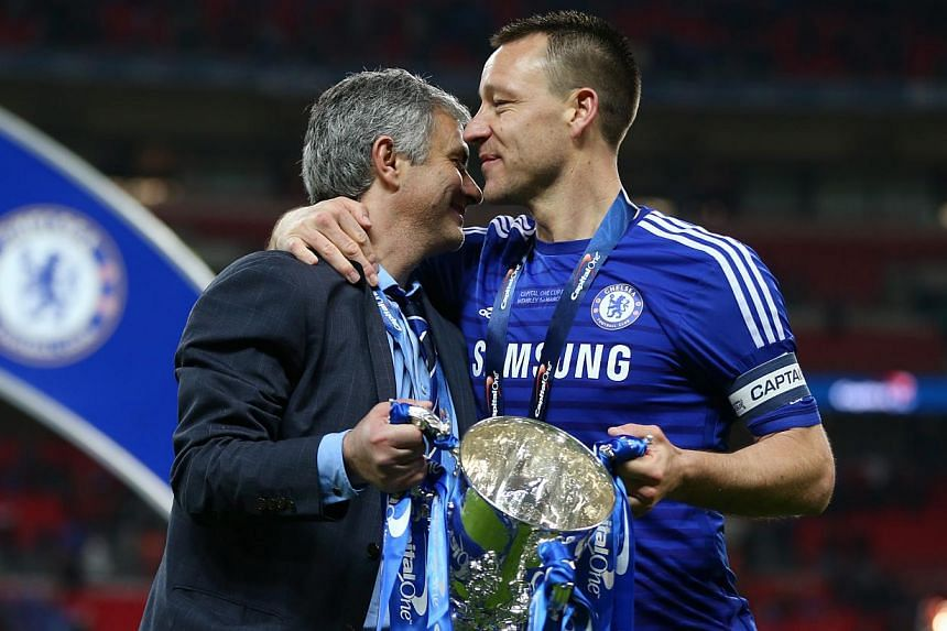 """Jose Mourinho (left) has assured Chelsea fans that John Terry, subject of a """"captain, leader, legend"""" banner that is on permanent display at Stamford Bridge, will be at the English Premier League club next season. -- PHOTO: REUTERS"""