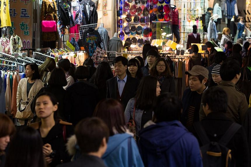 People walk through the Hongdae shopping district at night in Seoul, South Korea. The country's inflation hit its lowest level in more than 15 years in February owing to slumping oil prices, state data showed Tuesday, fuelling concerns about deflatio
