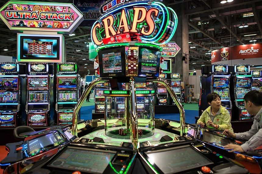 Visitors try a machine at the Global Gaming Expo Asia in the world's biggest gambling hub of Macau. Macau's gaming revenue fell by a record 48.6 per cent in February, a ninth straight month of decline. -- PHOTO: AFP