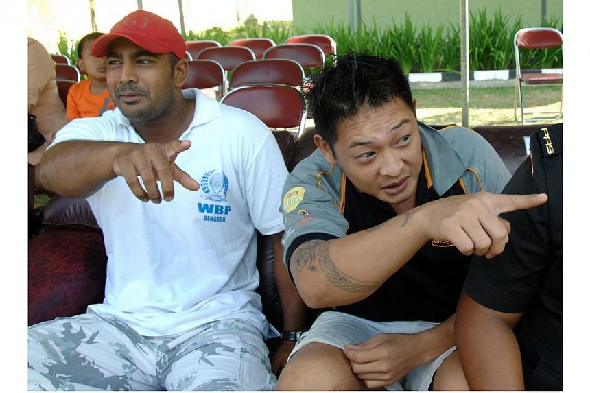 In this file photo taken on August 17, 2010, convicted Australian drug smugglers Myuran Sukumaran (left) and Andrew Chan (right) gesture as they sit inside Kerobokan prison in Denpasar, Bali. Indonesia's Attorney-General Prasetyo said preparatio