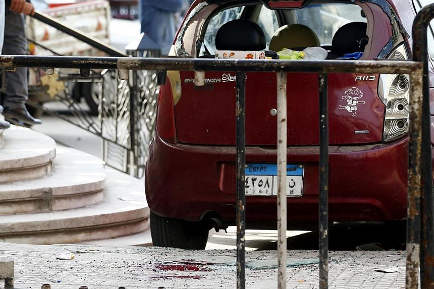 Blood stains are seen on the ground as security officials inspect the scene of a car bomb blast in front of The High Court in downtown Cairo on Monday. At least eight people were wounded, security sources said. -- PHOTO: REUTERS