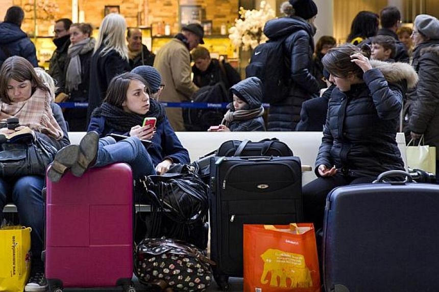 Passengers sit and wait at the Eurostar train terminal at St Pancras International station in London on Monday, after a fatality on the line in Kent. -- PHOTO: AFP