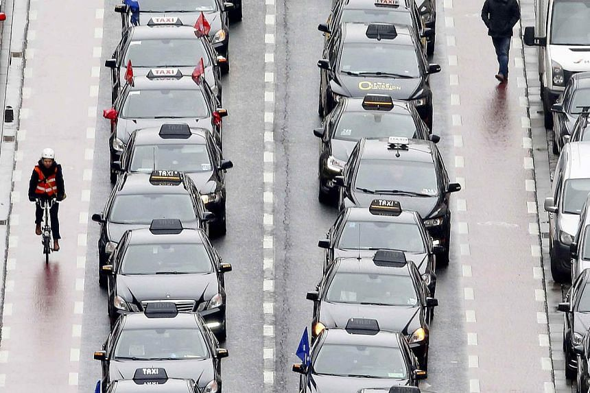 axi drivers line a street during a protest against online ride-sharing company Uber, in central Brussels on Tuesday. -- PHOTO: REUTERS
