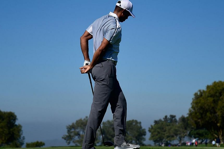 Tiger Woods holds his back after playing his tee shot on the 15th hole of the north course during the first round of the Farmers Insurance Open at Torrey Pines Golf Course on Feb 5 In La Jolla, California. -- PHOTO: AFP